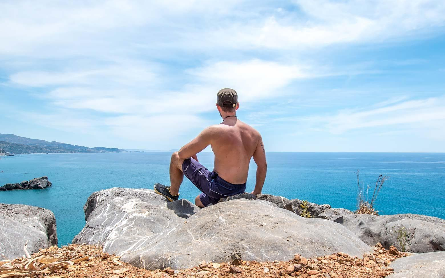man sitting on a rock in greece