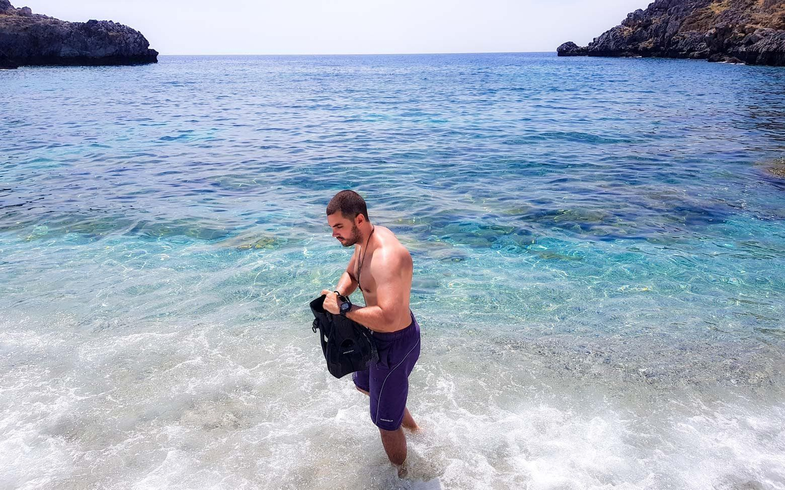 man preparing to snorkel on a greek beach