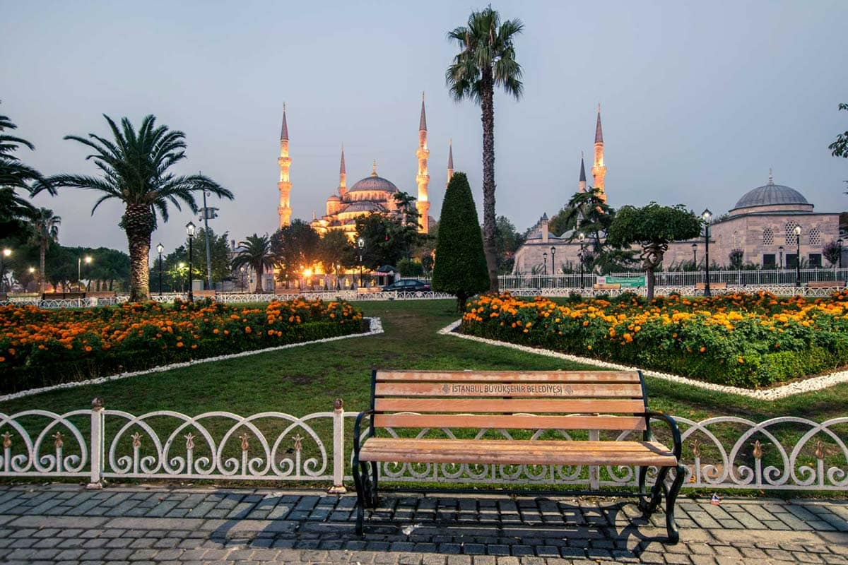bench-in-front-of-a-garden-with-a-mosque-in-the-back