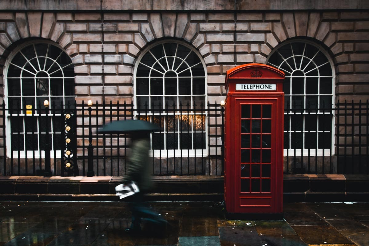 manwith-umbrella-walking-in-front-of-a-red-telephone-cabin
