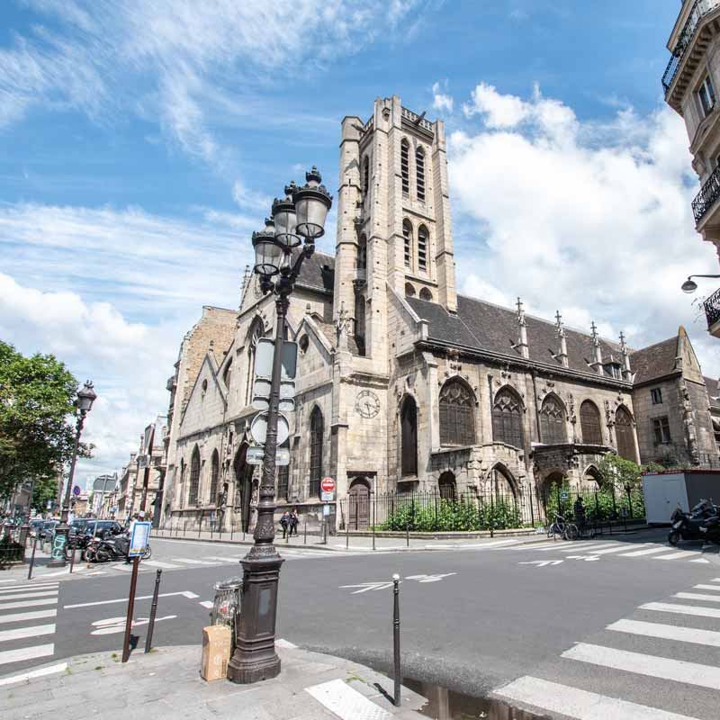 Streets in Paris with an old church in the background