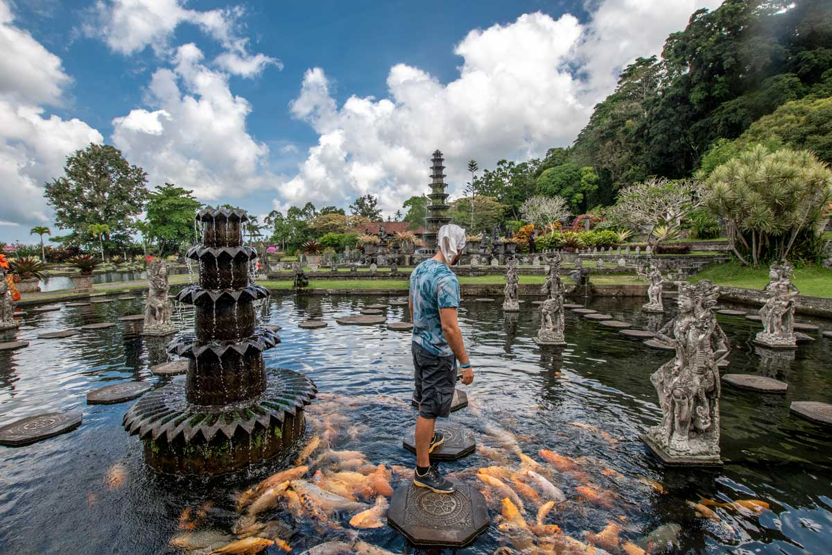 what indonesia is famous for - man taking a photo in a picturesque garden in bali