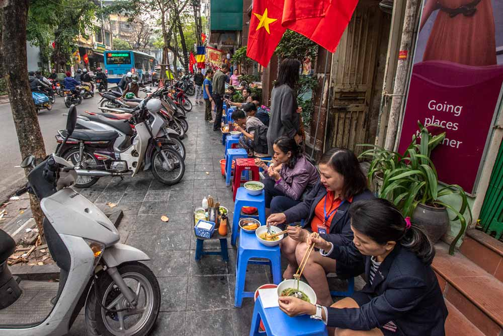 people eating street food on the pavement in hanoi