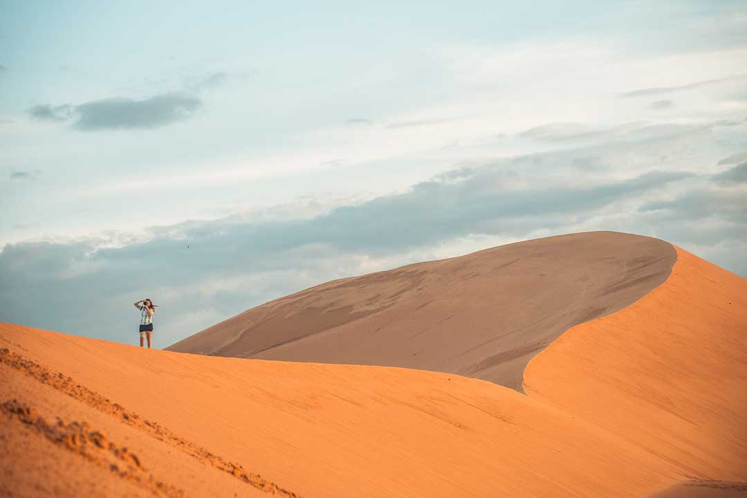 girl-taking-photos-on-a-sand-dune