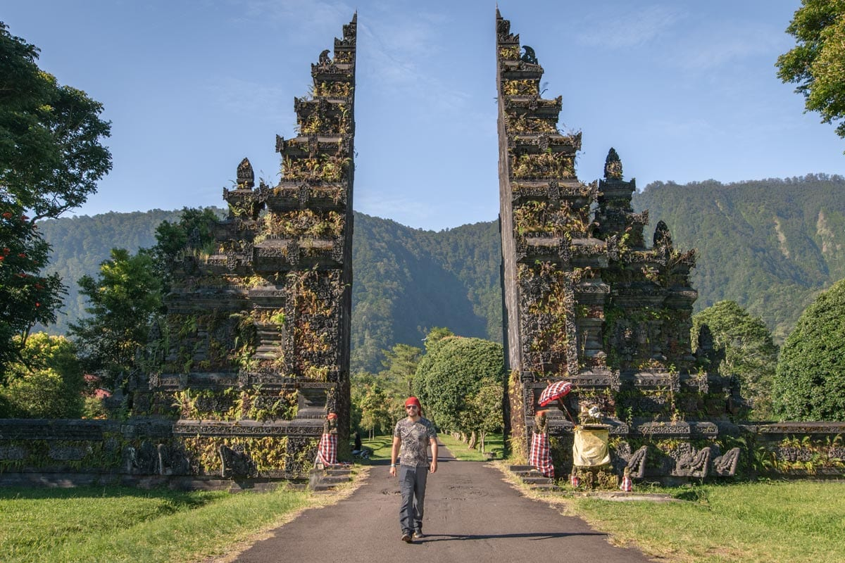 man-walking-in-front-of-a-traditional-balinese-stone-gate