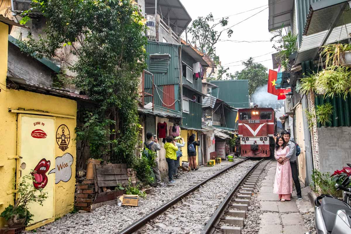 tourists taking photos on train street in hanoi
