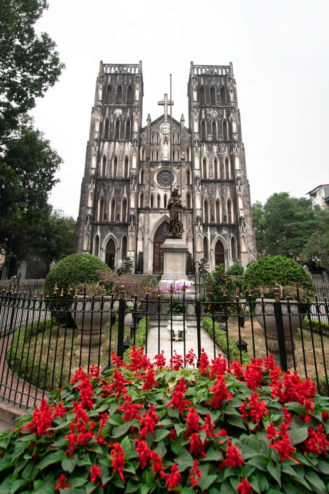 hanoi-bucket-list-french-cathedral-with-red-flowers-in-front