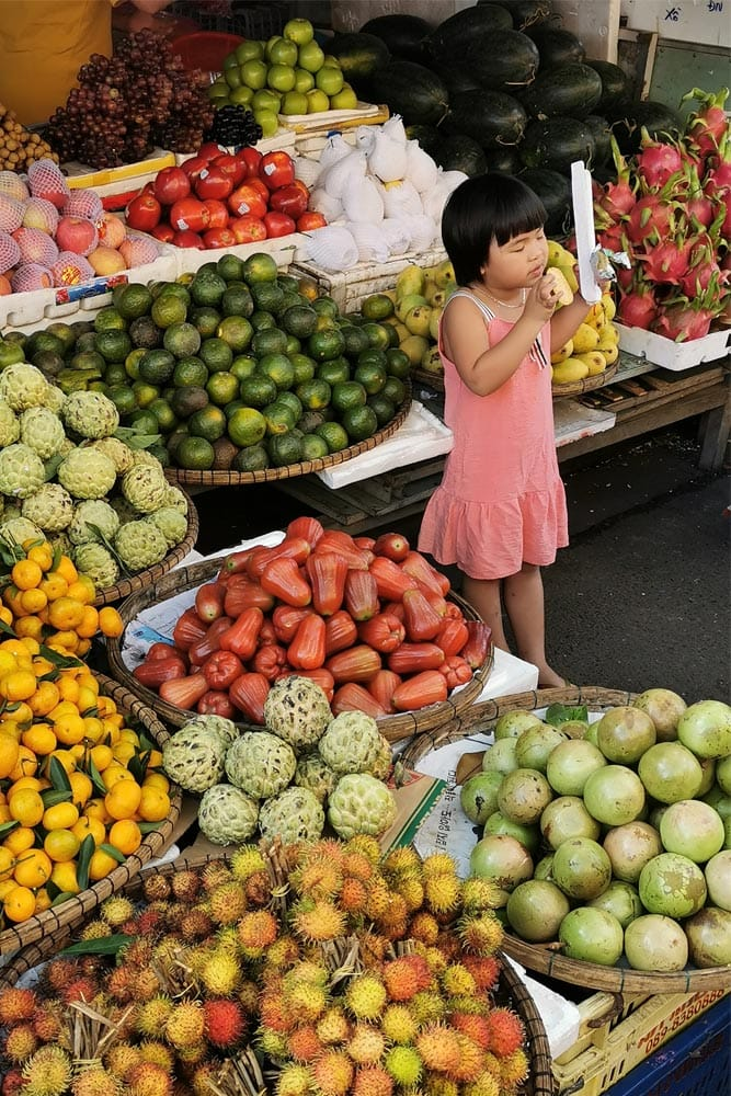 vietnamese-girl-surrounded-by-baskets-of-fruit