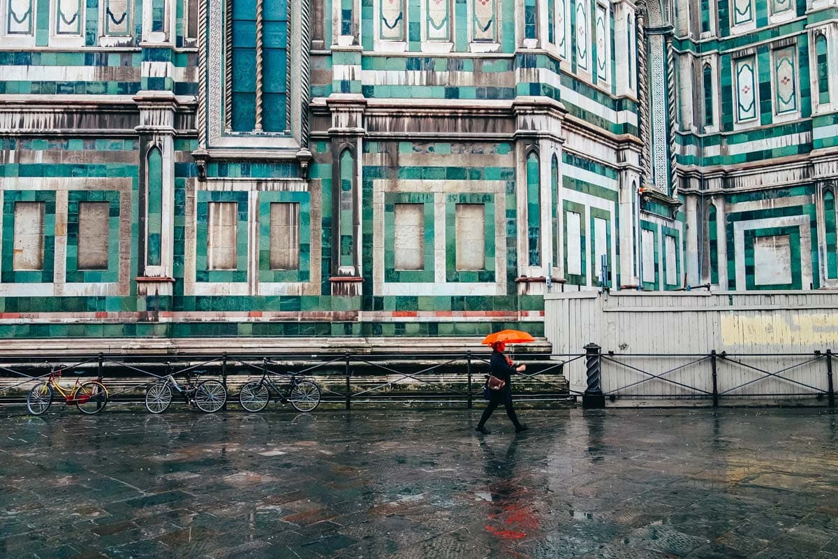 man-with-orange-umbrella-walking-in-front-of-colorful-building