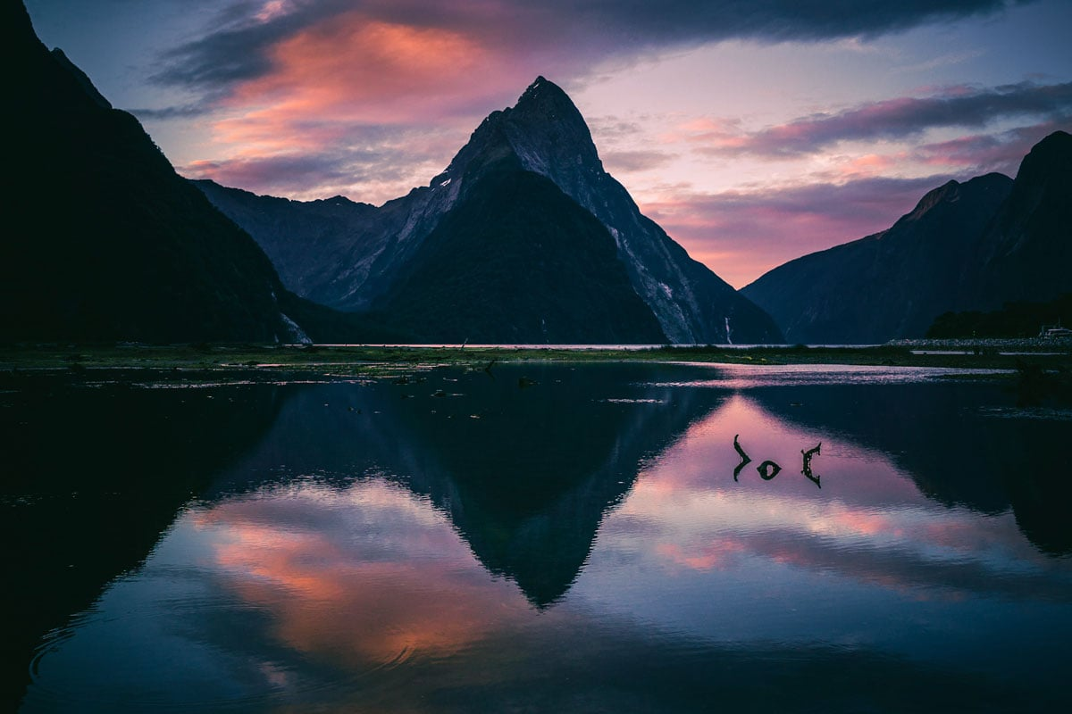 mountains-of-milford-sound-reflectin-in-the-water-on-sunset