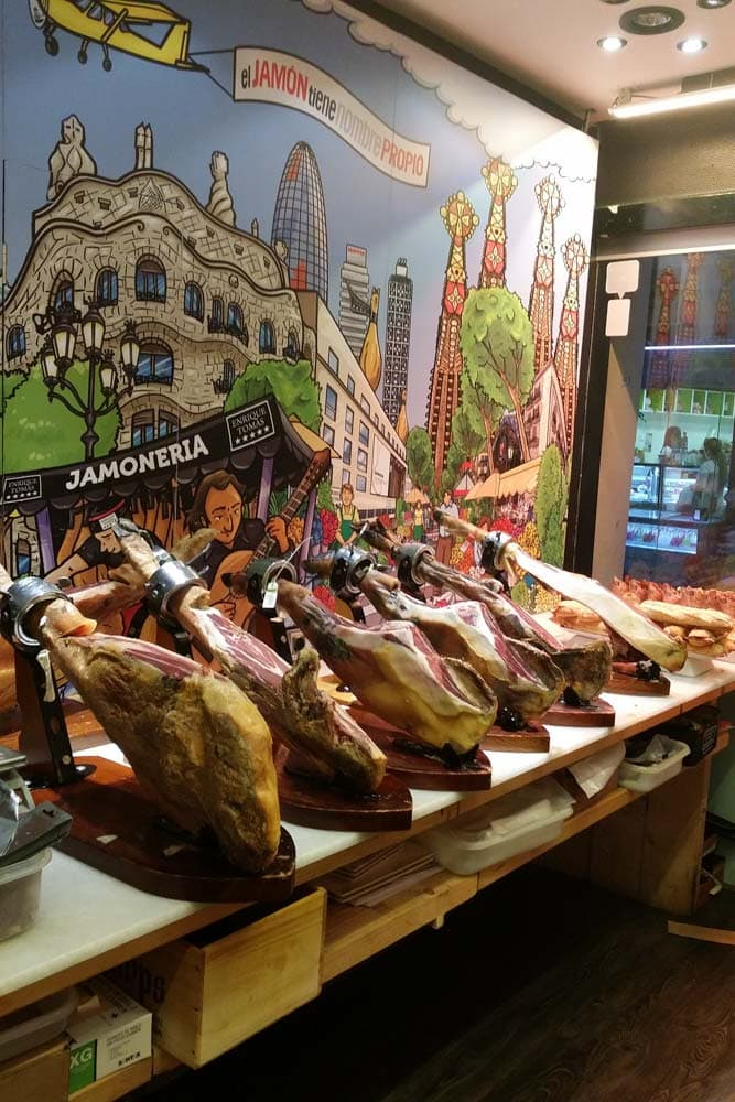 a-row-of-jamons-with-colorful-barcelona-background