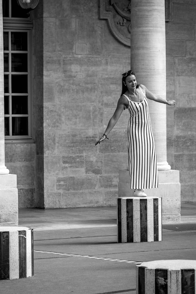 girl-posing-for-a-photo-on-a-column-black-and-white