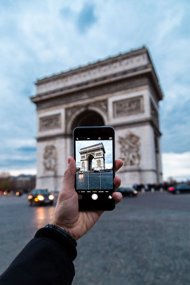 man-taking-a-phone-photo-of-arc-de-triomphe