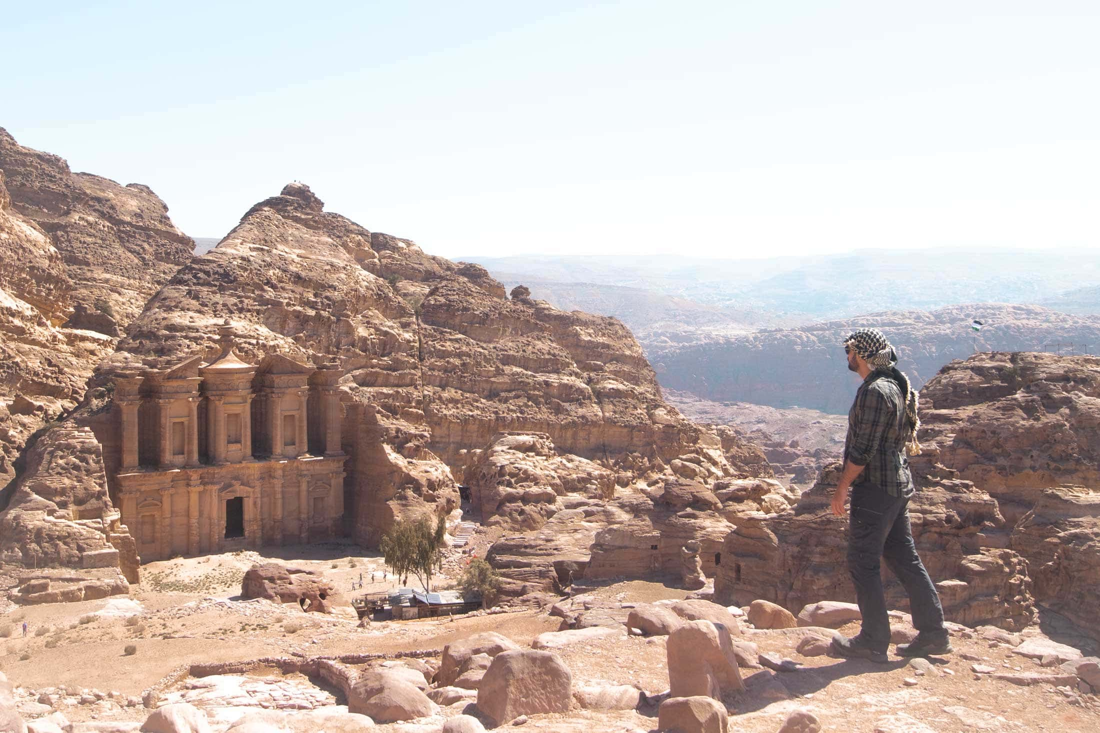 man standing in a desert with the monastery of petra in the distance