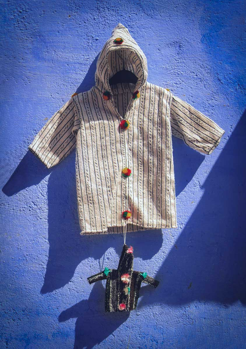 traditional-moroccan-djellaba-hung-on-a-blue-wall