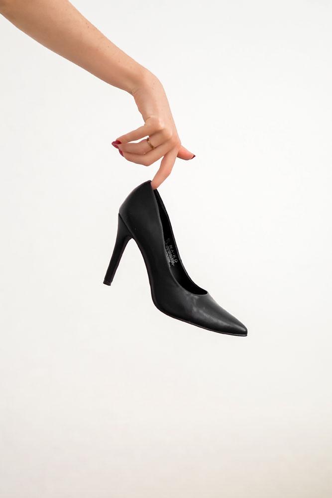 a-hand-holding-a-black-high-heel-shoe