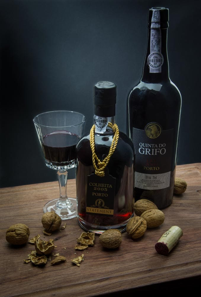 a-table-with-two-port-wine-bottles-and-nuts