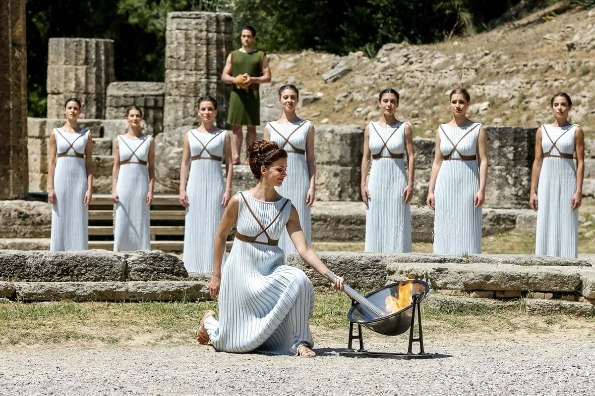 girl-in-traditional-greek-attire-lightning-up-an-olympic-torch