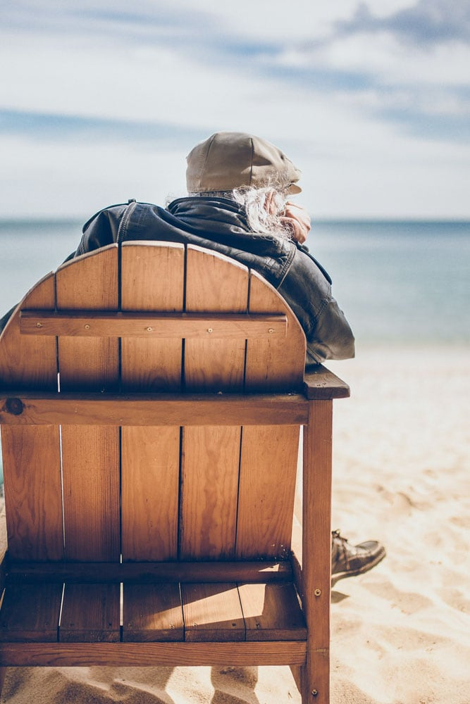 old-man-sitting-on-a-chair-on-the-beach-watching-the-ocean