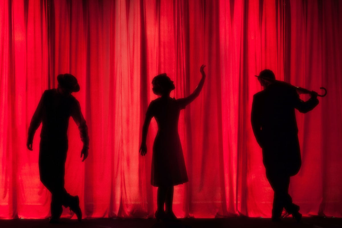 silhouettes-of-three-actors-behind-a-red-curtain