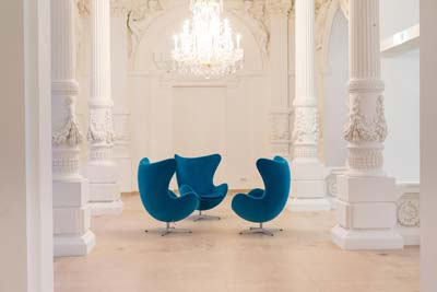 white room with three blue chairs