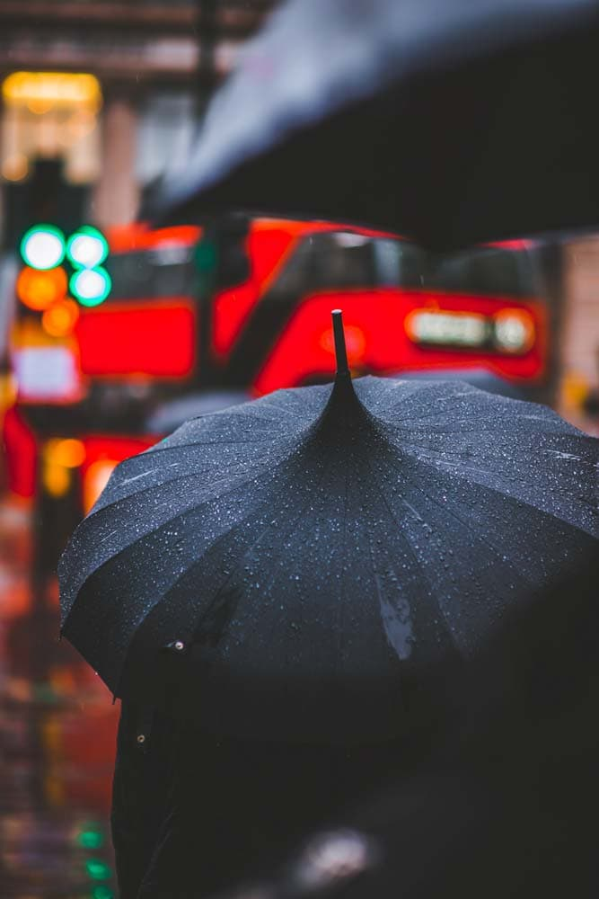 red-wet-umbrella-with-red-bus-blurred-in-the-background