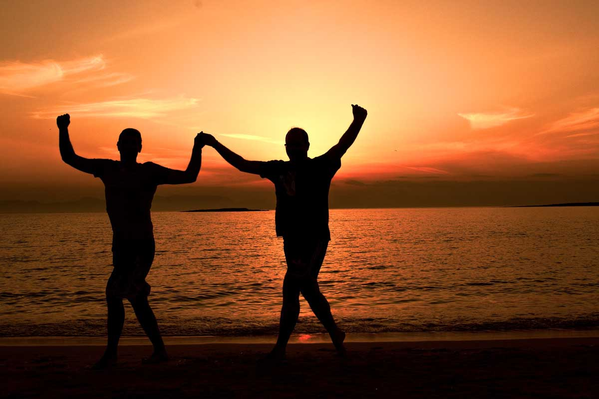 silhouettes-of-two-men-dancing-sirtaki-on-the-beach