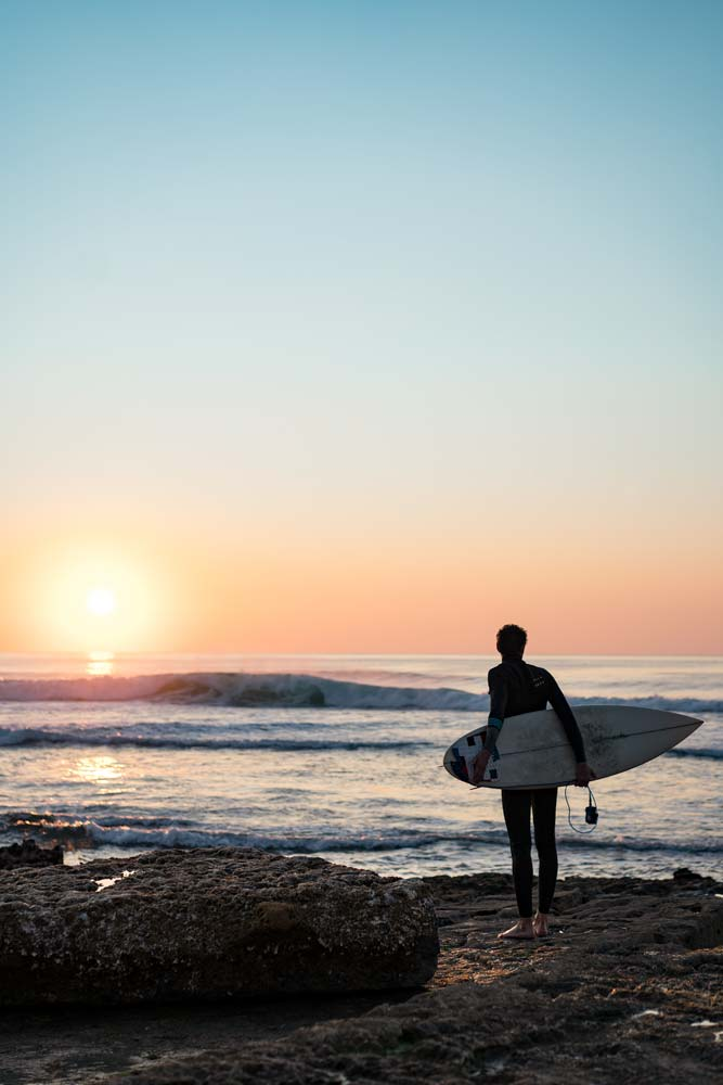 fun-portugal-facts-man-with-a-surf-board-standing-on-the-beach