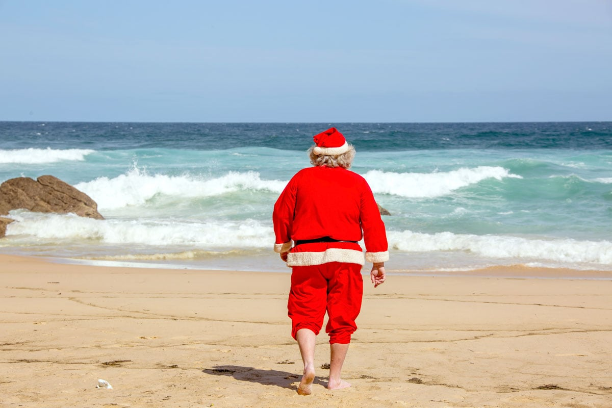 man-in-santa-outfit-walking-on-the-beach