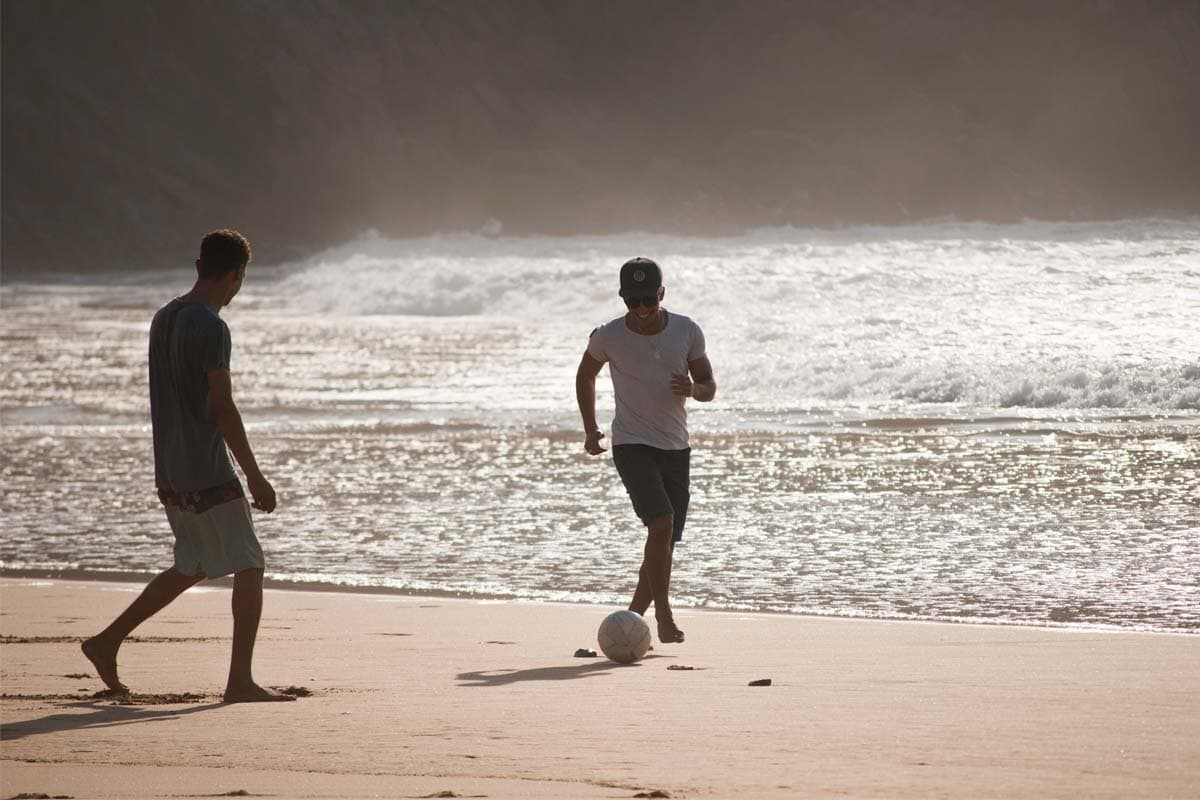 two-men-playing-football-on-the-beach