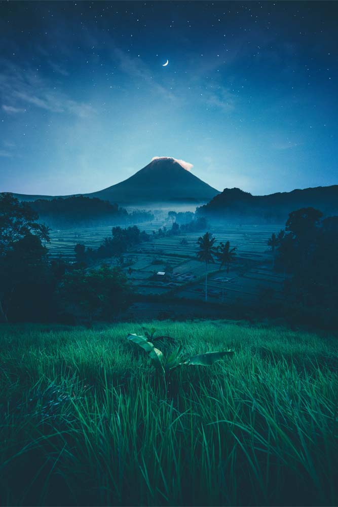 what-indonesia-is-famous-for-volcano-with-rise-farns-in-front-of-it-at-night